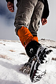 Hiker walking in snow, ascend to Unnutz Mountain (2078 m), Rofan Mountains, Tyrol, Austria