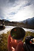 Hiker holding a cup, Koegl alp (1432 m), descent from Unnutz Mountain (2078 m), Rofan Mountains, Tyrol, Austria