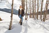Young woman leaning against a tree in snow, Spitzingsee, Upper Bavaria, Germany
