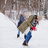 Two young women enjoying snowball fight, Spitzingsee, Upper Bavaria, Germany