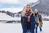 Two young women in snow, Spitzingsee, Upper Bavaria, Germany