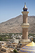 View from Nizwa Fort of the minaret of the As Sultan Qaboos Mosque with the Hajar Mountains in the background, Al Jinah, Nizwa, Ad Dakhiliyah Governorate, Oman.