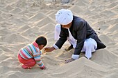 India, Rajasthan, Pipasar, Bishnoi elder and grandson building small sand dunes in the temple courtyard  Pipasar is Guru Jambeshwars birthplace and a major site of pilgrimage for the Bishnoi community