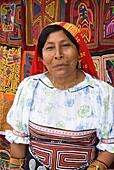 Kuna woman and molas in background, Playon Chico village, San Blas Islands also called Kuna Yala Islands, Panama
