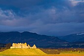 Scotland, Scottish Highlands, Cairngorms National Park  Dramatic light bathes the Ruthven Barracks, with the Monadhliath Mountains overlooking the ruins
