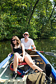 young couple canoeing along the Wakenitz river, along the former German border between East and West, area so called Amazona of the North, Schleswig-Holstein, Germany