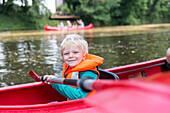 Boy kayaking on a canal, Plagwitz, Leipzig, Saxony, Germany