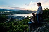 Two people enjoying the view of Edertalsperre dam at Lake Edersee in Kellerwald-Edersee National Park at sunset, Lake Edersee, Hesse, Germany, Europe