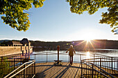 Man standing on a viewing platform in the light of the setting sun, looking to the Edertalsperre dam on Lake Edersee in Kellerwald-Edersee National Park, Lake Edersee, Hesse, Germany, Europe