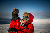 Couple using eclipse glasses, while watching the solar eclipse, Spitzbergen, Svalbard, Norway