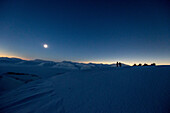 3 people with snowmobiles during the total solar eclipse, Spitzbergen, Svalbard, Norway