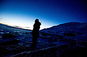Person with rifle standing and looking into the night at Spitzbergen, Spitzbergen, Svalbard, Norway