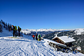 Several persons back-country skiing having a break at an alpine hut, Stubai Alps in the background, Gammerspitze, valley of Schmirn, Zillertal Alps, Tyrol, Austria