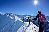 Three persons back-country skiing ascending on snow-ridge, Zillertal Alps in background, Gammerspitze, valley of Schmirn, Zillertal Alps, Tyrol, Austria