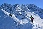 Several persons back-country skiing ascending on snow-ridge, Zillertal Alps in the background, Gammerspitze, valley of Schmirn, Zillertal Alps, Tyrol, Austria