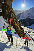 Two persons back-country skiing ascending through steep gully towards Schneespitze, Schneespitze, valley of Pflersch, Stubai Alps, South Tyrol, Italy