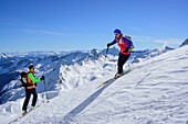 Man and woman back-country skiing downhill from Schneespitze, Schneespitze, valley of Pflersch, Stubai Alps, South Tyrol, Italy