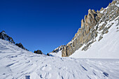 Snow erosion in front of rock wall of Monte Sautron, Valle Maira, Cottian Alps, Piedmont, Italy