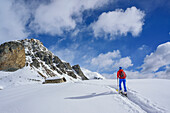 Woman back-country skiing walking towards snow-covered alpine hut, Rocca Senghi in the background, Monte Faraut, Valle Varaita, Cottian Alps, Piedmont, Italy