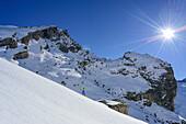 Woman back-country skiing ascending towards Monte Salza, crossing alpine hut, in background Rocca Senghi, Monte Salza, Valle Varaita, Cottian Alps, Piedmont, Italy
