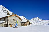 Woman back-country skiing passing alpine huts and ascending towards Monte Salza, Monte Salza, Valle Varaita, Cottian Alps, Piedmont, Italy