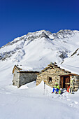 Woman back-country skiing having a break at alpine huts, Monte Salza, Valle Varaita, Cottian Alps, Piedmont, Italy