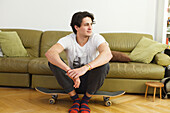 Young man at home, sitting on a skateboard, indoors