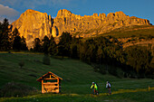 two mountain bikers at sunset in front of Latemar, Trentino Italy