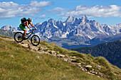 mountain biker on a single-trail before Pale di San Martino, Trentino Italy