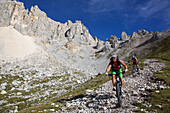 two mountain bikers on a single-trail at Latemar, Trentino Italy