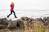A girl jumping over rocks at Sumner Beach, Christchurch, South Island, New Zealand