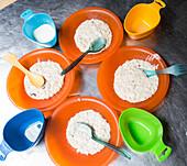 Plastic plates with porridge, breakfast at Hope Arm Hut, Fjordland, Lake Manapouri, South Island, New Zealand