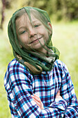 A girl protecting herself with a mosquito net against Black Flies, Fjordland, South Island, New Zealand