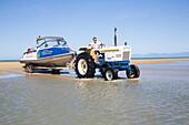 Taxiboote werden mit Traktor und Anhänger aus dem Meer geholt. Abel Tasman National Park, Südinsel, Neuseeland