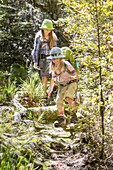 Zwei Mädchen wandern vom Binnenland zur Küste des Abel Tasman Nationalparks, Südinsel, Neuseeland