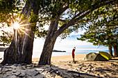 Eine Frau macht Yoga am morgen im Zeltlager am Strand der Apple Tree Bay, Abel Tasman Nationalpark. Südinsel, Neuseeland
