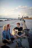 Julia, Daniella and Pavel sitting on the pier, hangout by the docks opposite the freeport, Petersala district, Daugava River, Riga, Latvia
