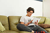 Young man sitting on the sofa, playing with his tablet