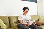 Junger Mann sitzt auf dem Sofa und spielt auf dem Tablet