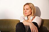 Junge Frau sitzt auf dem Sofa und träumt