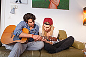 Young couple relaxing on the sofa, playing the guitar