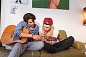 Junges Paar entspannt sich auf dem Sofa und spielt Gitarre