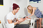 Young couple in the kitchen, playing with mobile and eating pizza