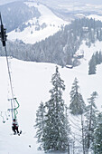 Snowboarder in single chair lift, Kampenwand, Alps, Bavaria, Germany