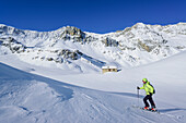 Woman back-country skiing passing at snow covered alpine hut with Monte Reghetta, Monte Faraut and Monte Gabel in background, Rocca La Marchisa, Valle Varaita, Cottian Alps, Piedmont, Italy