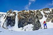 Woman back-country skiing ascending towards rockface with icefall, Grundschartner, Zillergrund, Zillertal Alps, Tyrol, Austria
