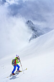 Woman back-country skiing ascending through clouds towards Grundschartner, Grundschartner, Zillergrund, Zillertal Alps, Tyrol, Austria