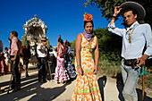 Pilgrims with oxcart and women wearing Flamenco dresses on a pilgrimage 'Nuestra Senora de El Rocio'  on the route La Raya Real from Seville to El Rocio, Huelva, Andalusien, Spanien