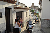 People and scooter on a cobblestone lane in Sacromonte with the Alhambra in the background, Granada, Andalusia, Spain
