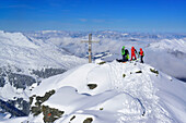 Group of persons back-country skiing standing at summit of Pallspitze, Pallspitze, Langer Grund, Kitzbuehel range, Tyrol, Austria